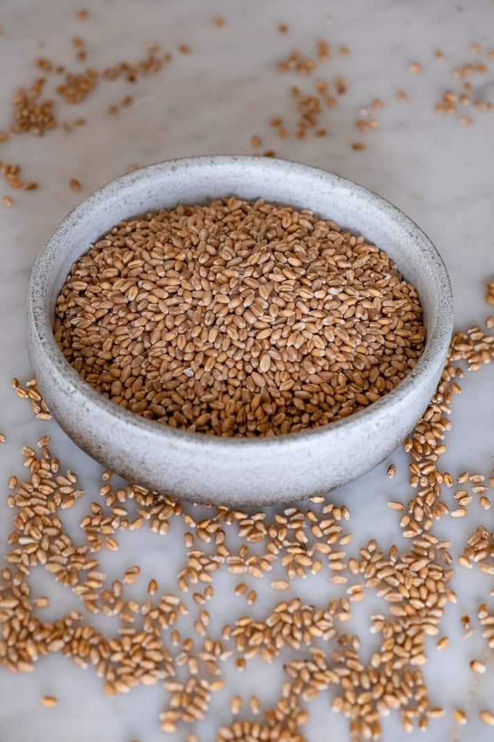 Wheat berries fill a clay bowl with some spilled over onto a marble countertop.