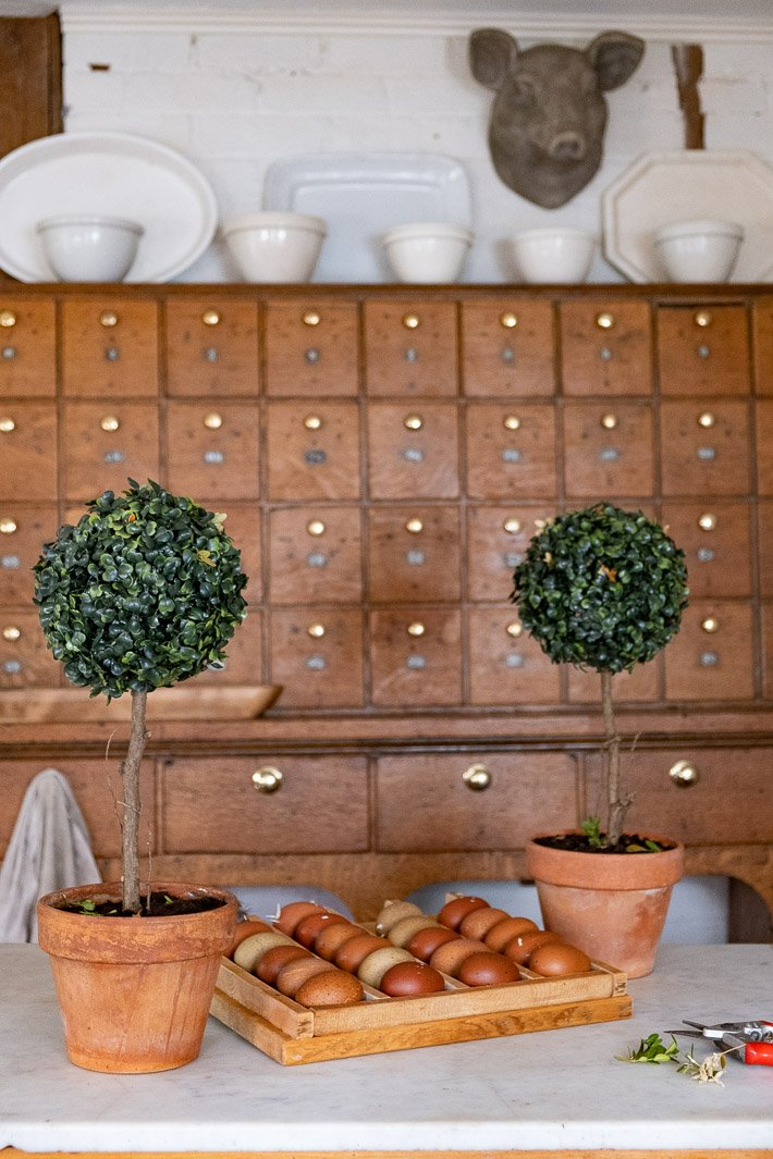 Artificial DIY topiaries in farmhouse kitchen.