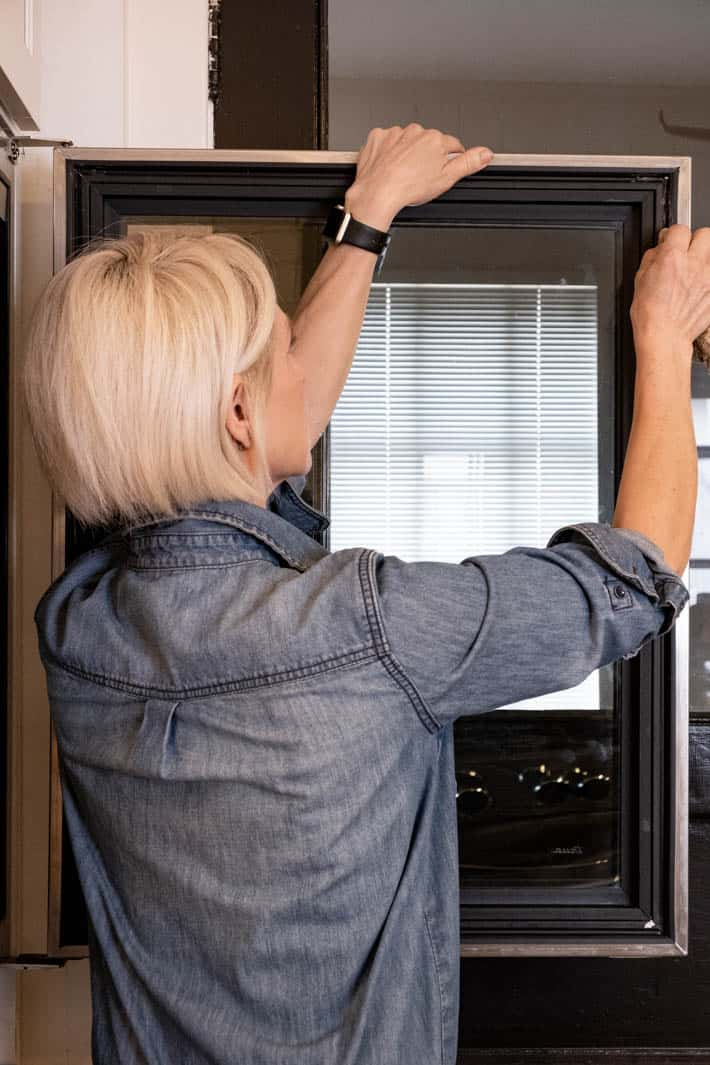 Blonde woman in denim shirt, thoroughly wiping the channel that holds the door gasket.