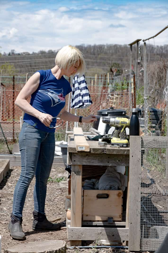 Karen Bertelsen assesses her tools laid out on a garden potting bench before building a hinged hoop house. Blue skies seen in the background.