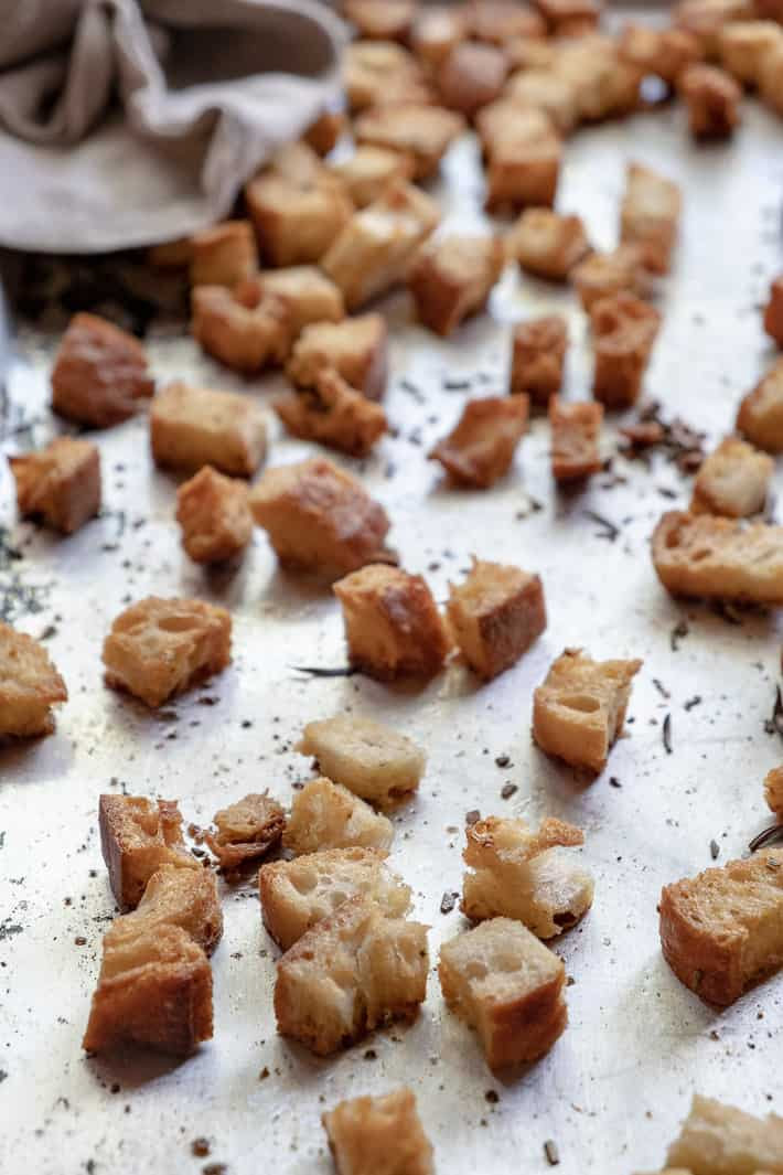 A close up view of browned, airy croutons on a baking sheet with a linen tea towel to the side.