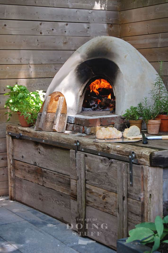 DIY cob pizza oven with a barnboard and antique brick heart, shows a roaring fire inside and freshly baked bread.