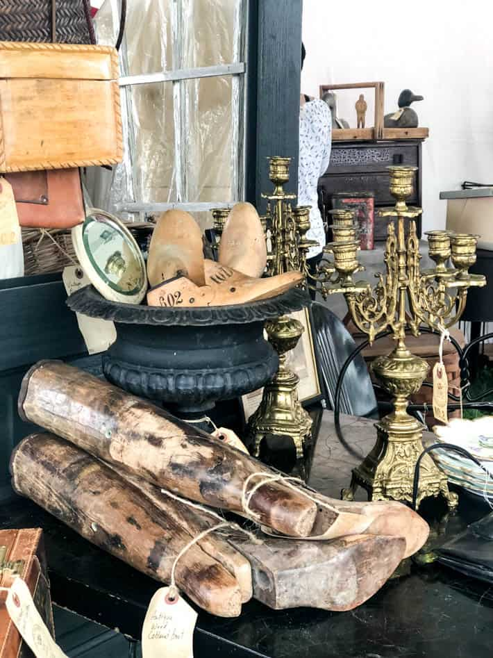 Assortment of antique show finds sitting on a table including tall boot forms, shoe forms in a black cast-iron urn and antique brass candelabras.