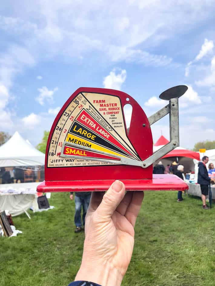 A woman's hand holding up an red, antique Sears, Roebuck & Company egg scale at the Christie Antique Show. Green grass and cloudy blue sky in background.