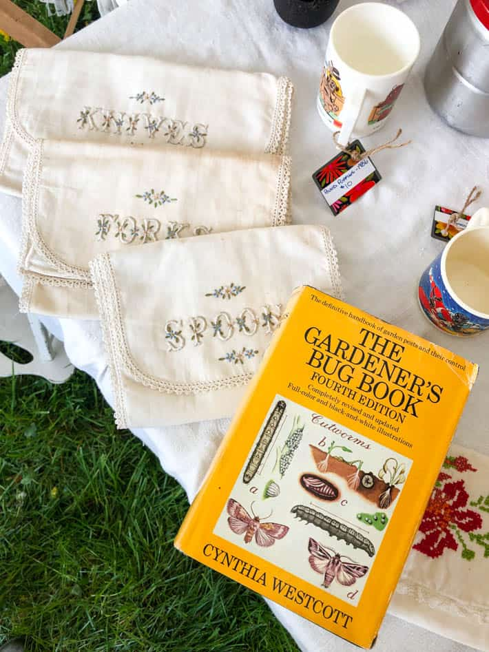 "Embroidered cutlery pouches beside ""The Gardener's Bug Book, Fourth Edition"" on outdoor table covered with embroidered tablecloth."