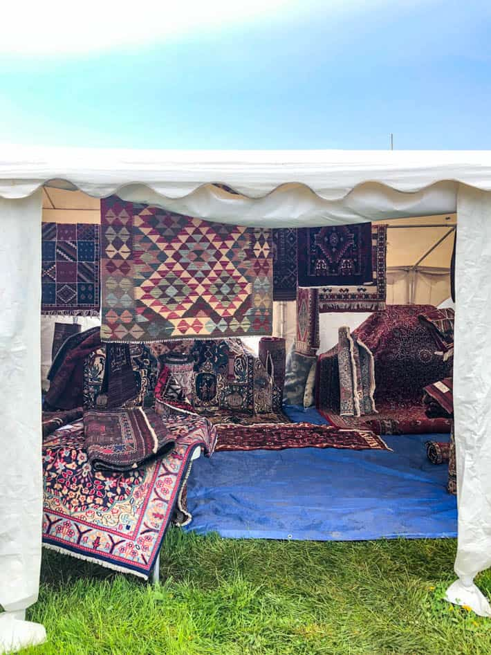 White tent containing many kilim rugs on ground and hanging up at the Christie Antique Show.