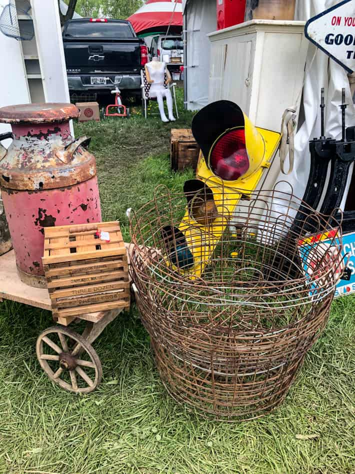 As assortment of finds at the antique show including rustic pink milk urn, wooden egg crate, antique traffic lights and wire baskets.