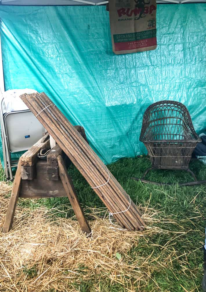Long sticks that are tied together leaning on rustic wooden sawhorse in front of blue tarp with wicker chair to the right.