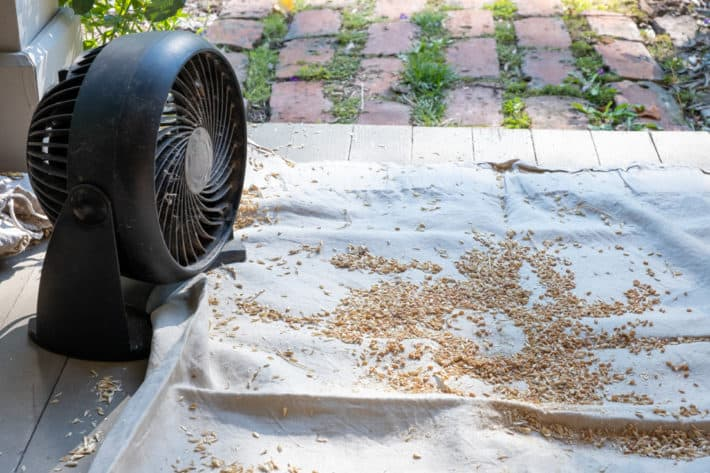 A small cheap fan on a porch directed at wheat with chaff to help with winnowing.