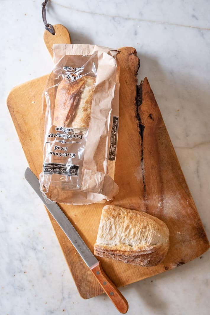 Paper and plastic bag used to bring fresh bread home from the bakery on a wood cutting board.