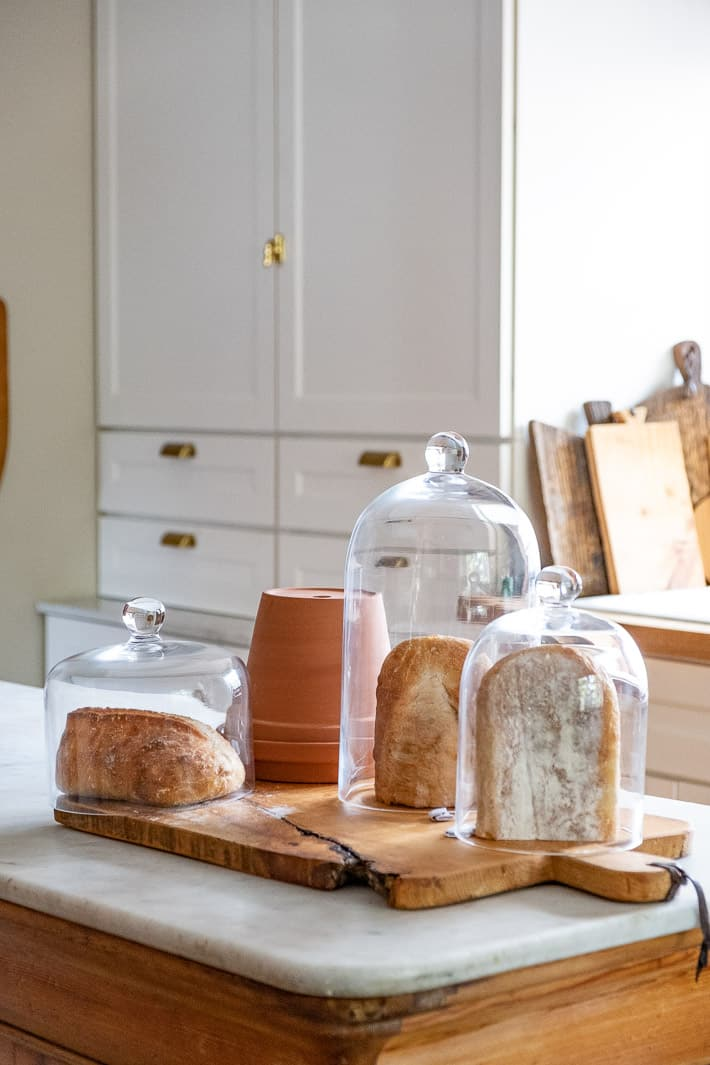 Experimenting with storing bread shows half loaves stored under glass domes and a clay pot on a white marble kitchen island.
