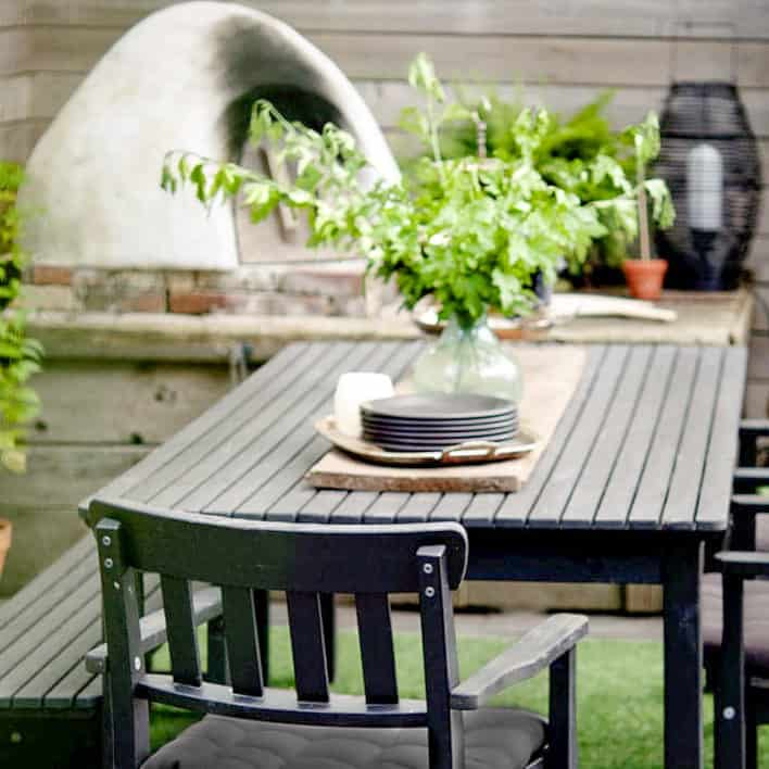 Elegant black, wood outdoor table set up in front of a homemade cob pizza oven and hearth.