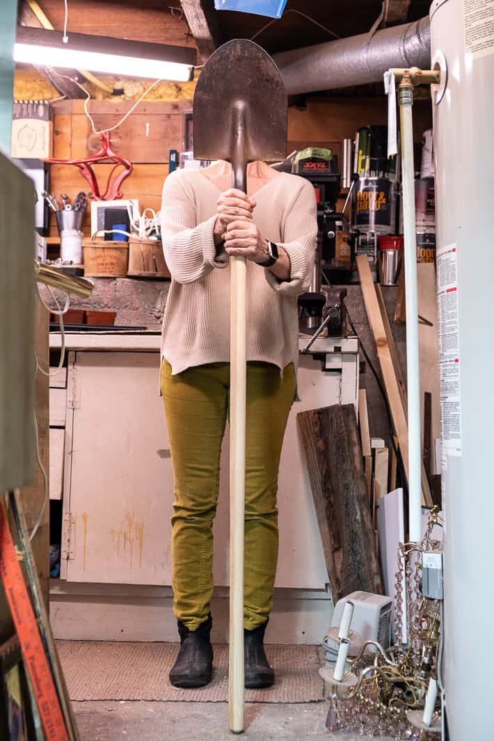 Karen Bertelsen seats shovel handle in the midst of a messy basement workshop.