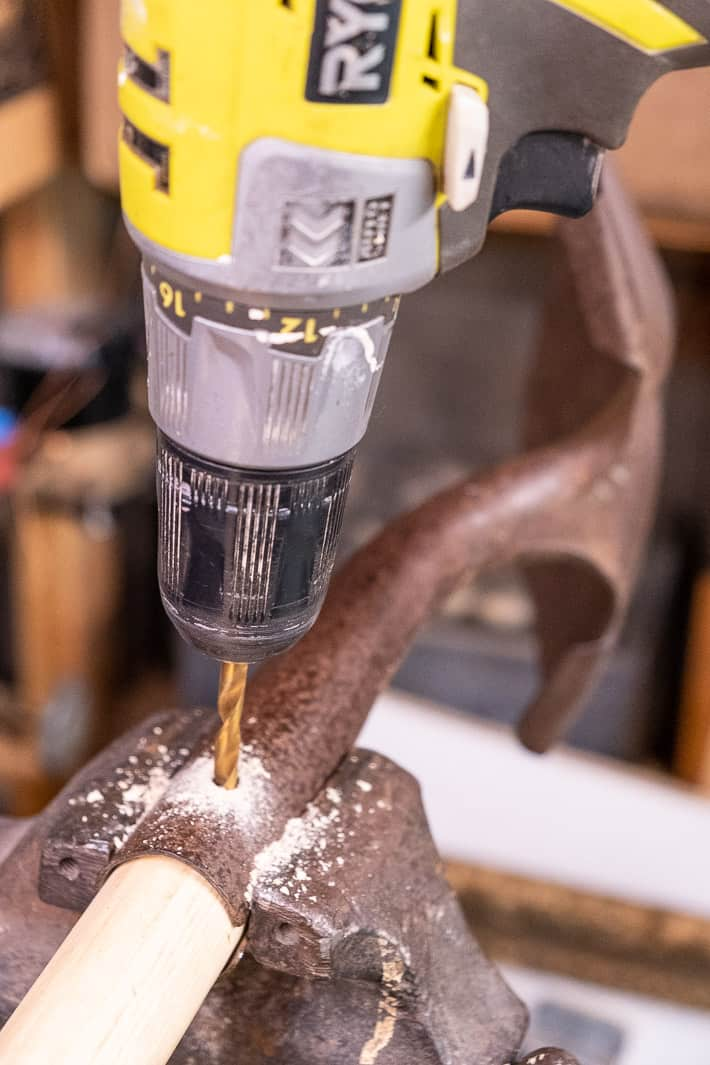 Shovel head held tightly in a vice while a drill kicks up sawdust, creating a hole in the new handle for a rivet to go through.