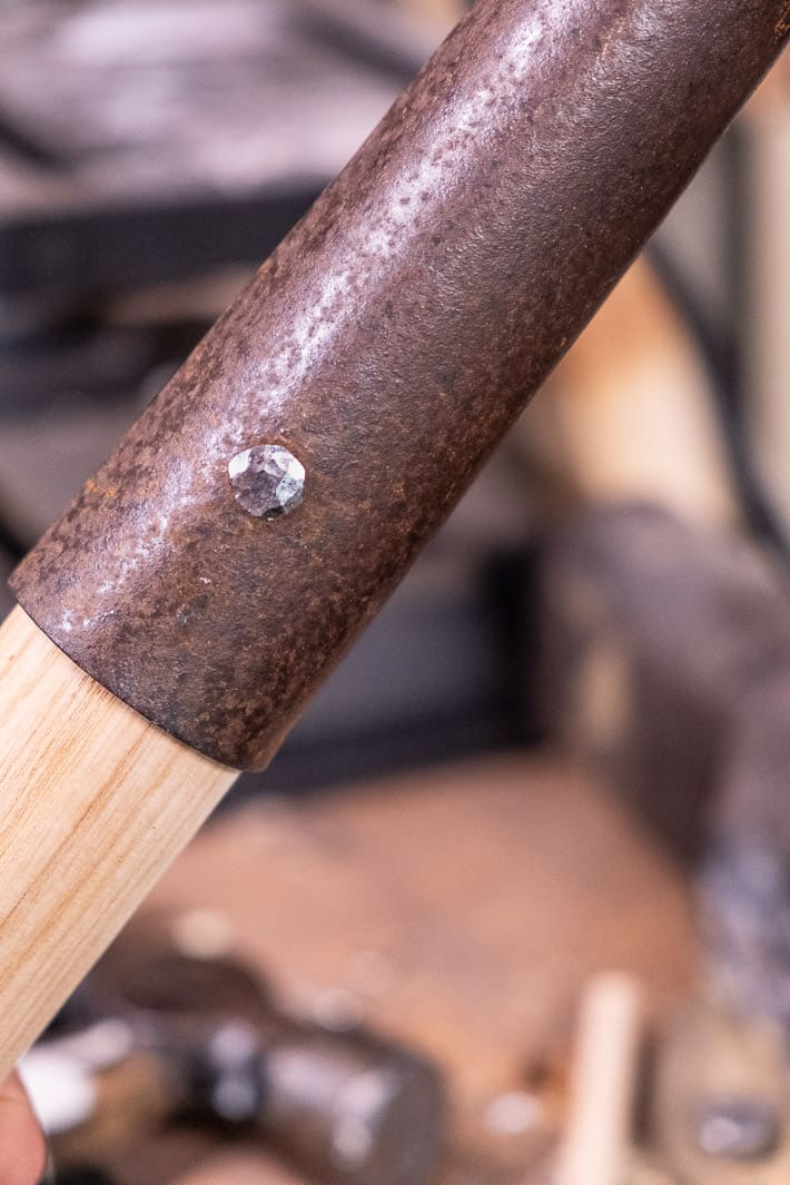 Gleaming hand hammered rivet that's been flatted out while replacing an old shovel handle with a new one.