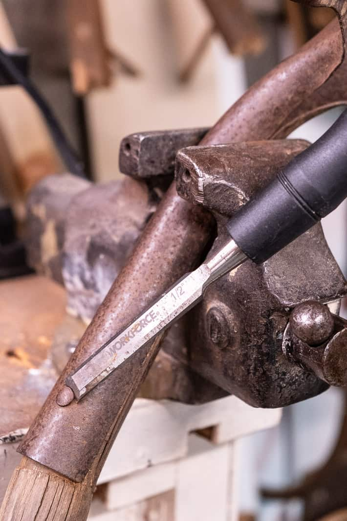 Chisel sliding under head of rivet head on shovel handle being held in vice.