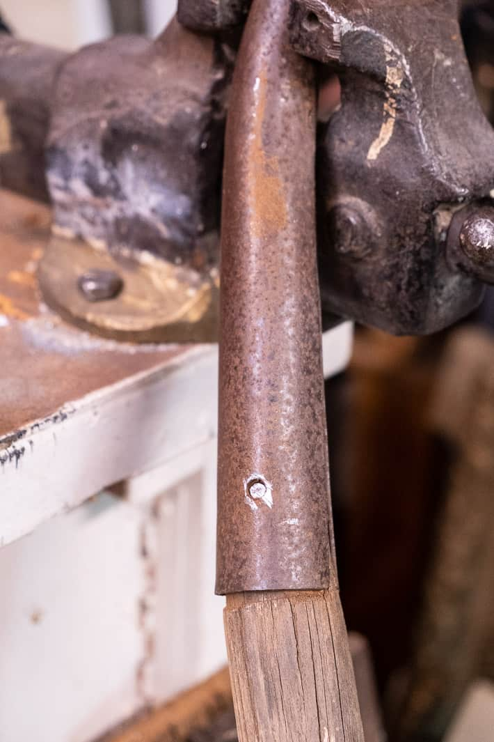 Rusted shovel handle being held tightly in a vice showing rivet with the head removed by hawcksaw.