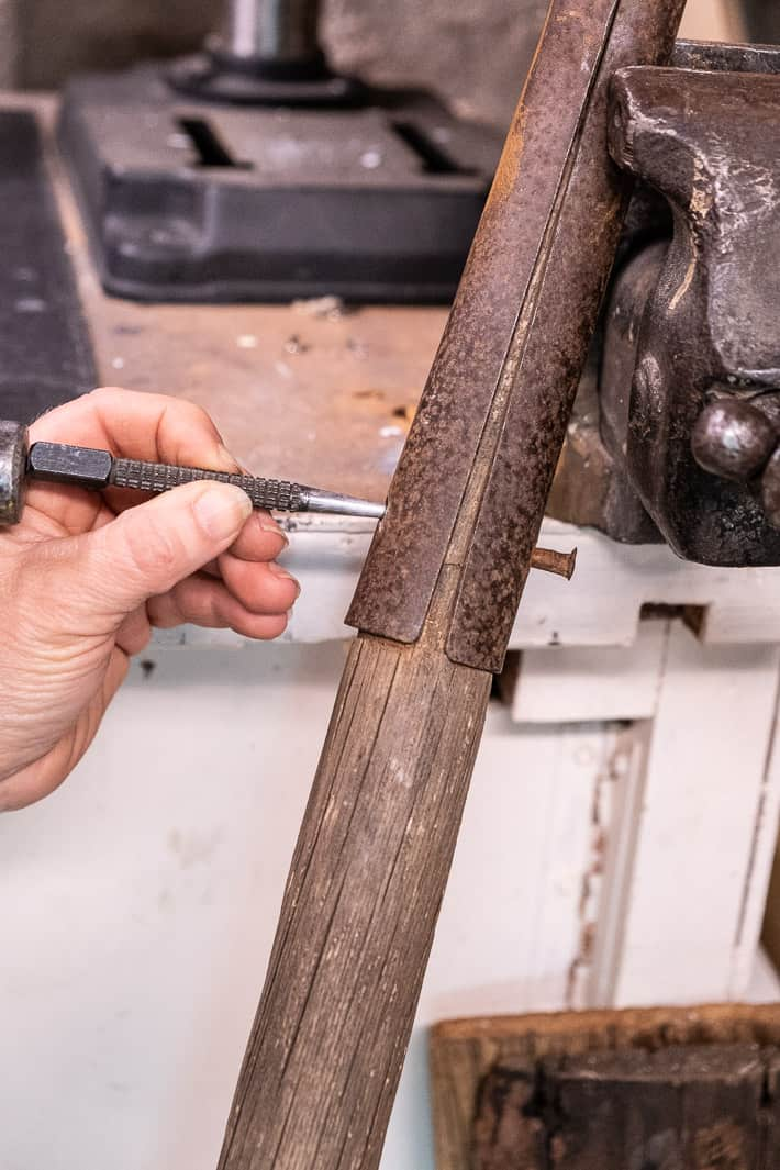 Punching through a rivet from old, rusted shovel head to remove old handle.