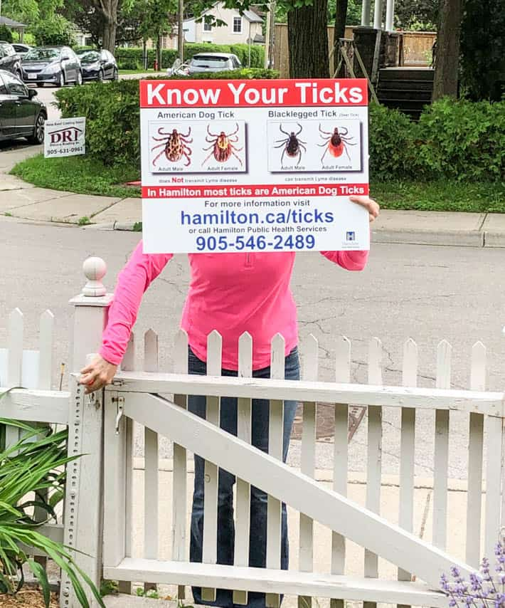 Tick identification sign being held up by a woman in a pink shirt as she enters picket fence gate.