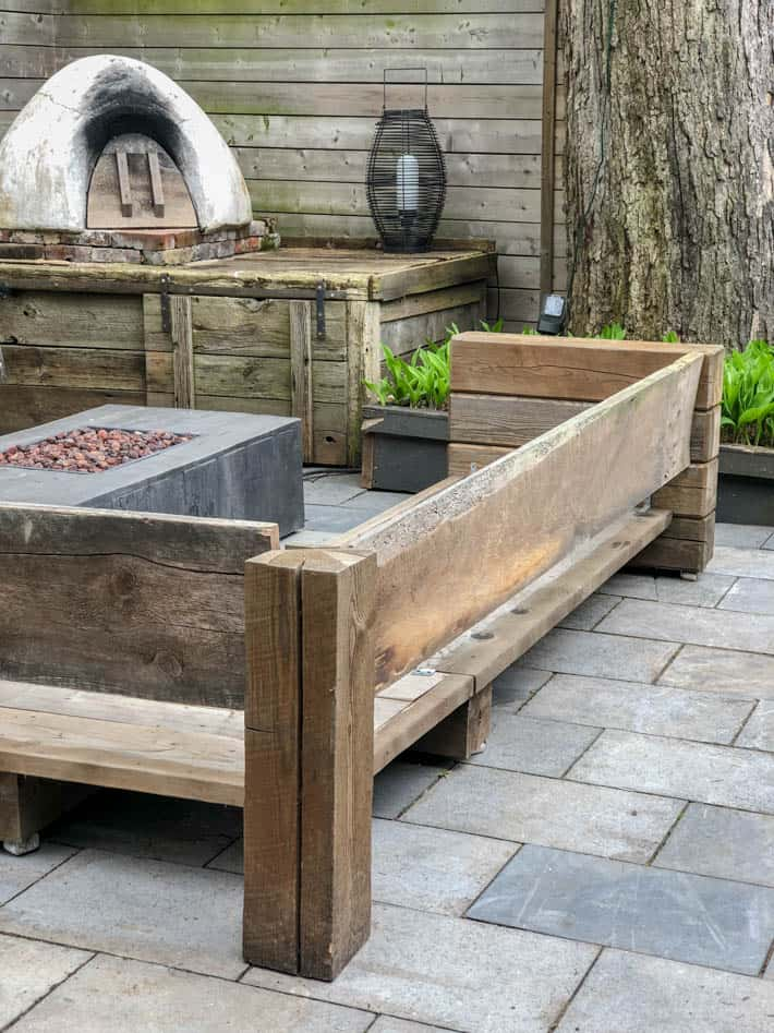 DIY outdoor wooden Restoration Hardware sectional sofa without cushions in front of unlit outdoor fire pit and pizza oven. Outdoor lantern sits beside pizza oven with large tree to the right.