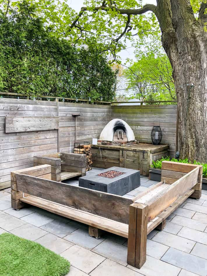 DIY outdoor wooden Restoration Hardware sectional sofa without cushions in front of unlit outdoor fire pit and pizza oven. Wooden fence and large tree in background.