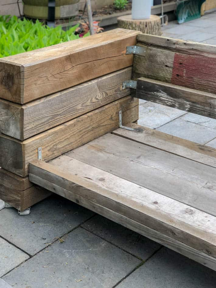 DIY outdoor wooden Restoration Hardware sectional sofa without cushions showing L brackets used for corner joinery.