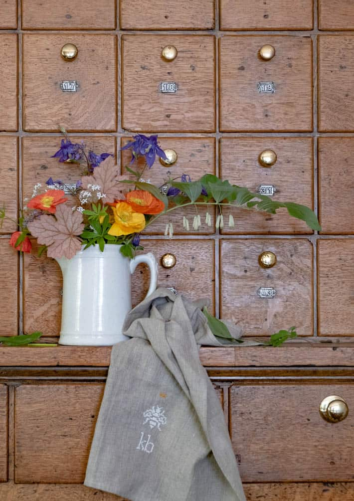 Ironstone crock filled with flowers and greenery with beige linen towel draped beside it; both sitting on antique wooden hardware cabinet.