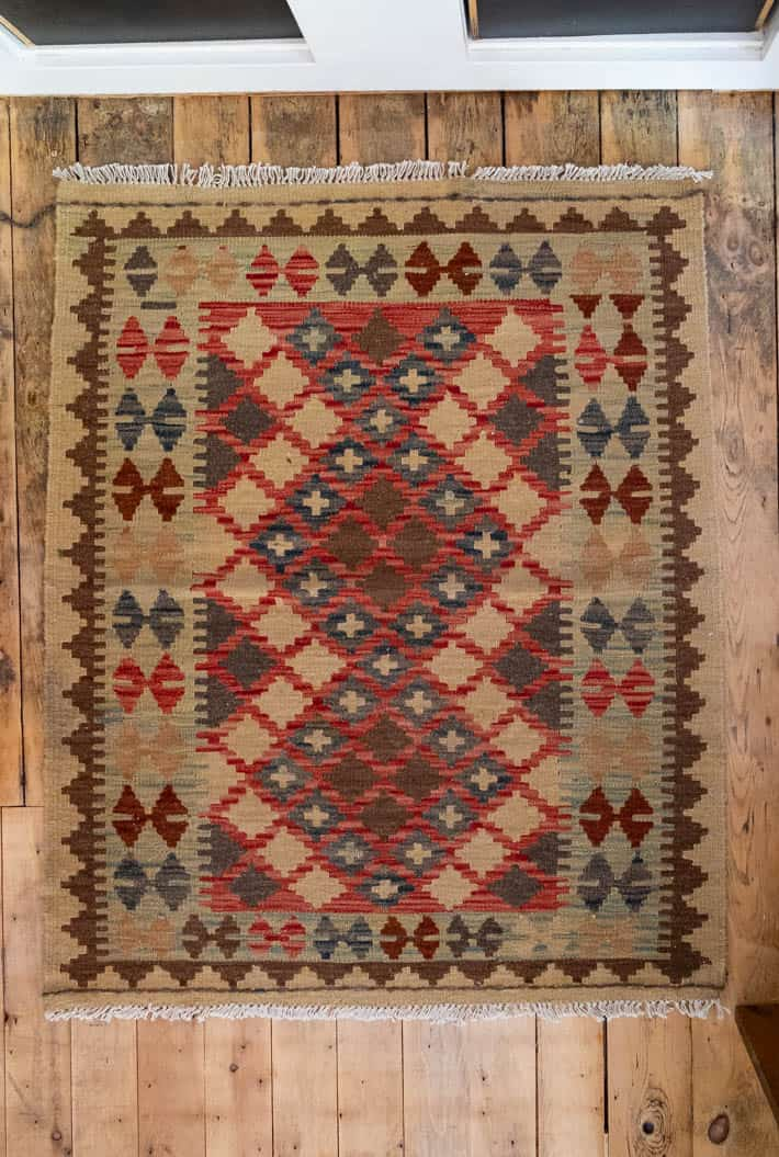 Patterned brown, tan, red and blue Turkish kilim rug bought at the Christie Antique Show on rustic wooden floor.