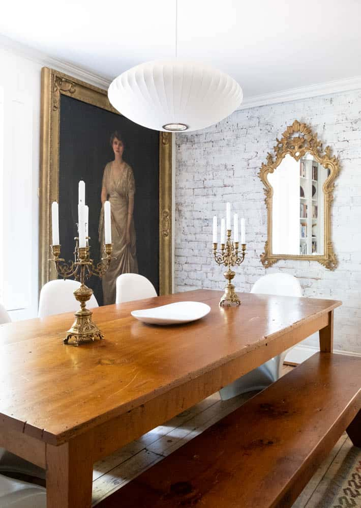 Pair of antique brass candelabras with unlit candles and a white plate sitting on wooden farmhouse table surrounded by mid-century dining room decor . Modern white chandelier positioned over the table.