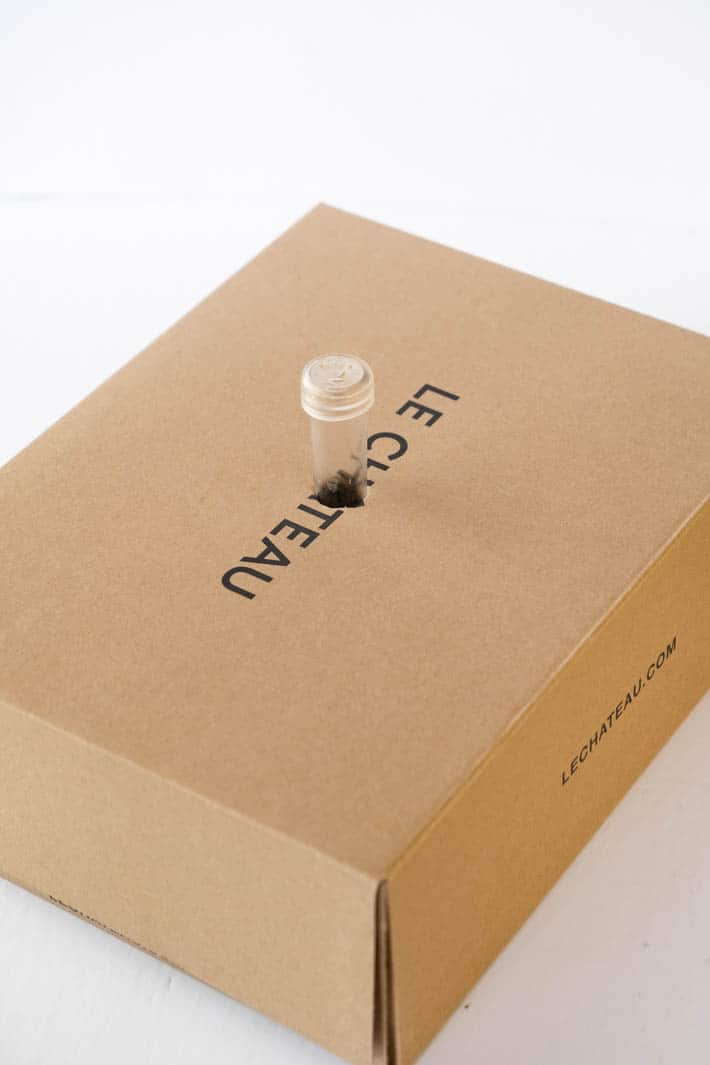 Brown Le Chateau box with translucent floral vial inserted into hole in center of box on white background.