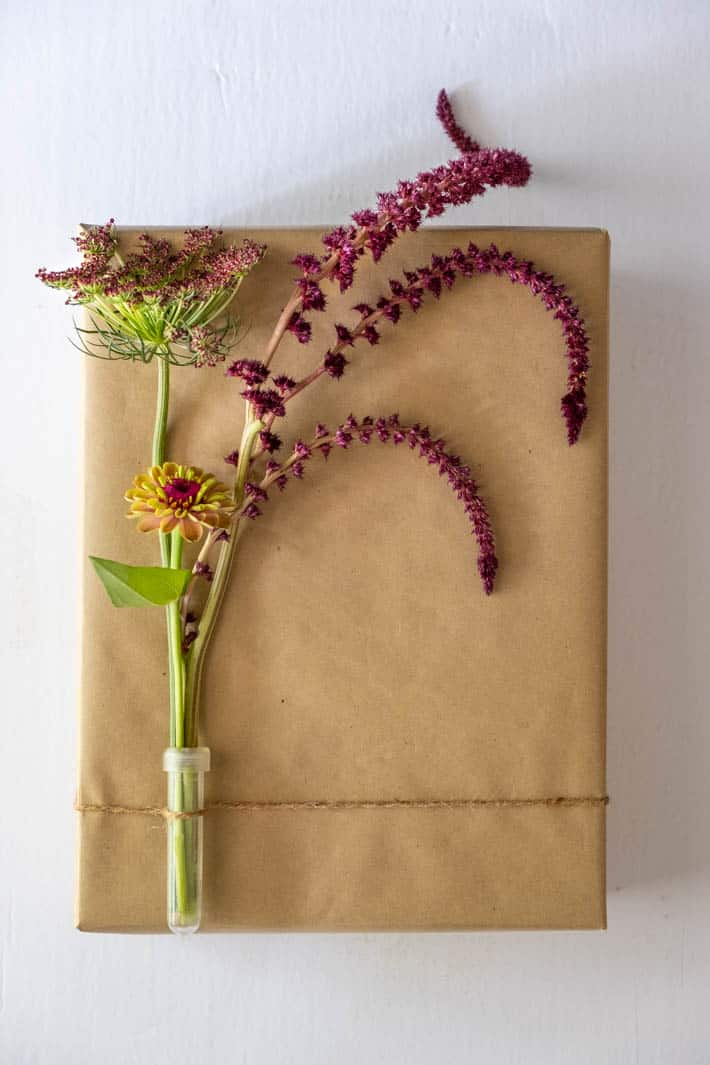 Chocolate Lace Flower, Queen Red Lime Zinnia, Opopeo Amaranth in clear floral vial tied with twine to gift wrapped in brown paper on white background.