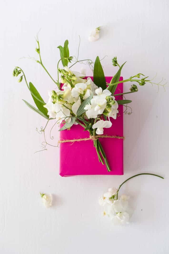 Overhead shot of gift wrapped with fuchsia paper topped with flower bow containing Perennial Sweet Peas, Sweet Pea tendrils and greenery tied on with twine on white background. Loose sweet pea blooms on table in foreground.