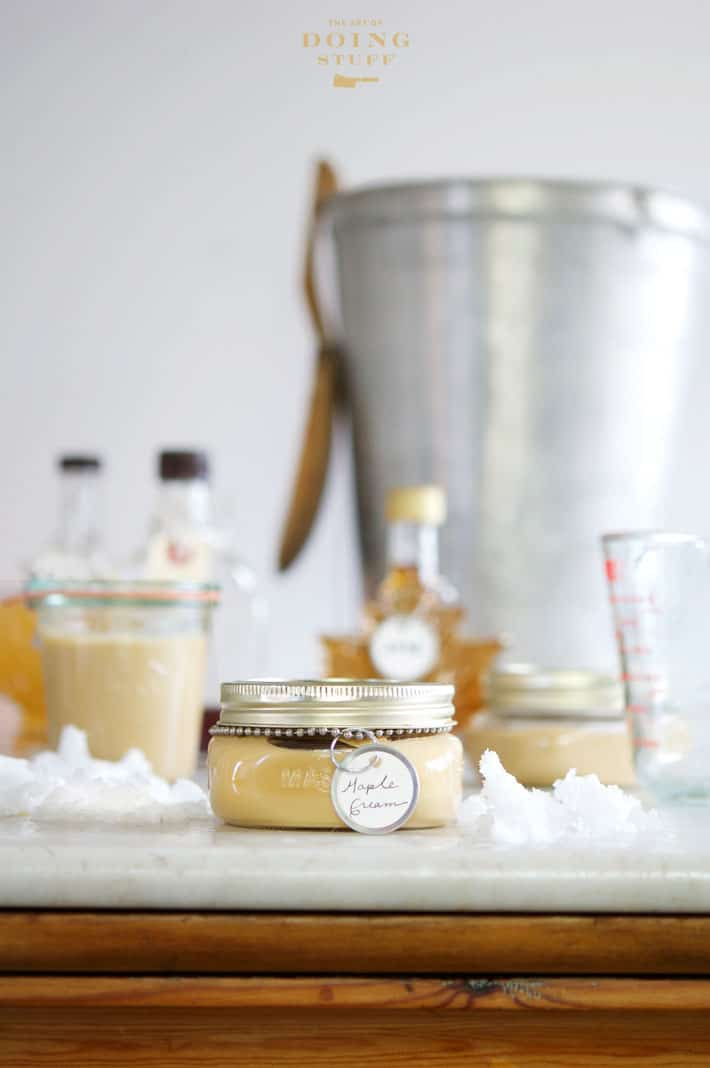 Display of mason jars filled with maple cream and bottles of maple syrup on an antique pine counter with a marble top. Sap bucket with wood spoon in background.