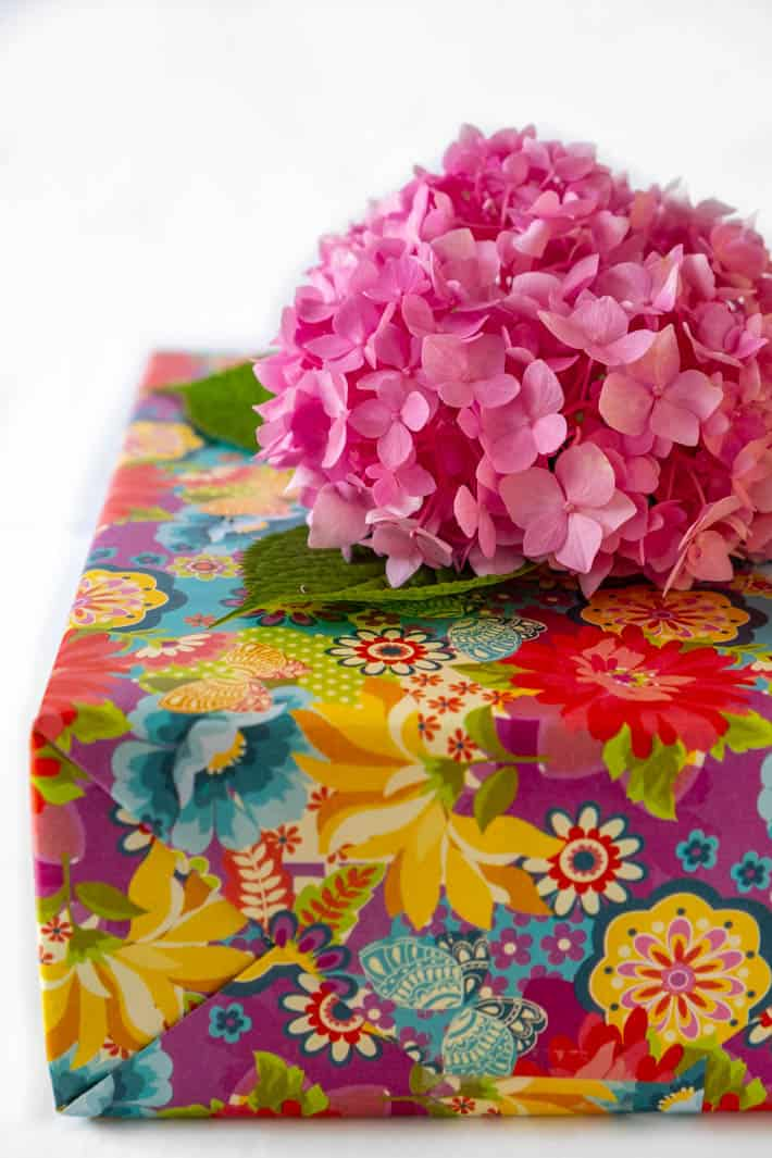 Pink hydrangea flower bow inserted into gift wrapped in floral paper on white background.