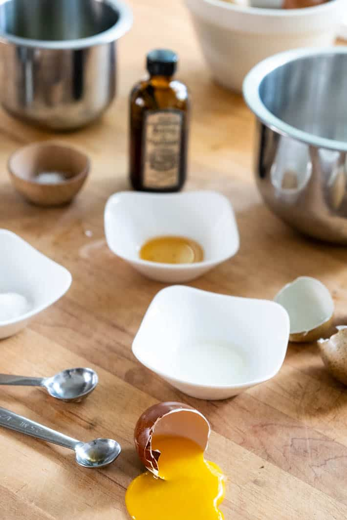 Cracked eggshells, silver measuring spoons, bottle of vanilla extract and white and stainless-steel bowls on wooden countertop.
