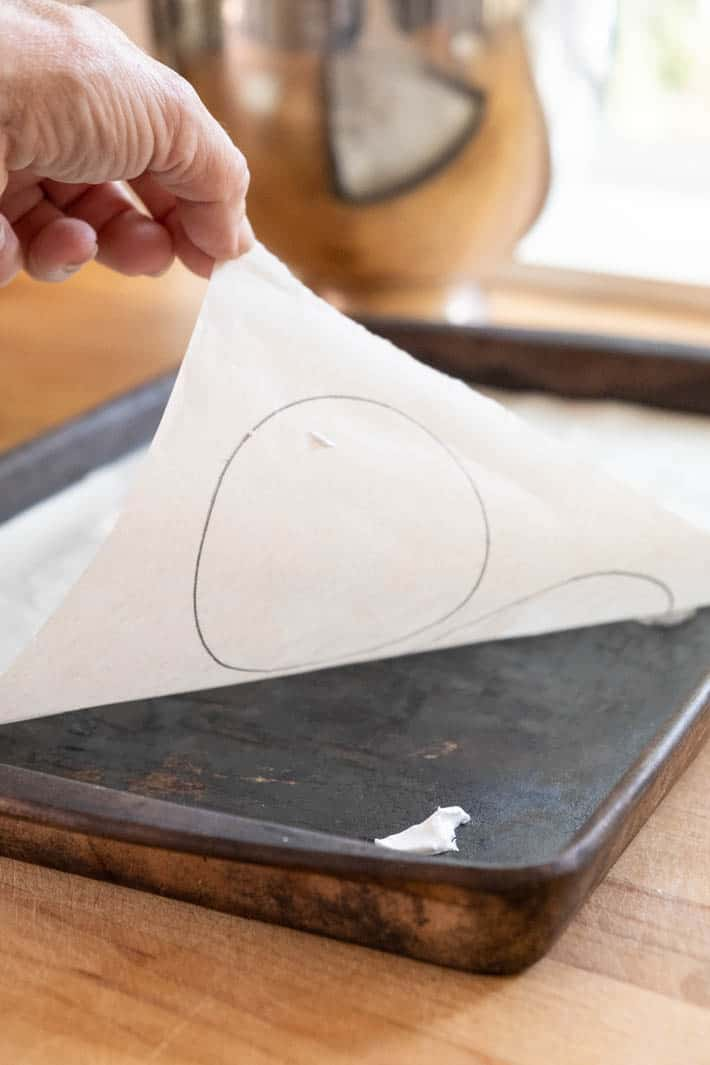 Hand placing parchment paper with circles drawn on it onto a baking tray.