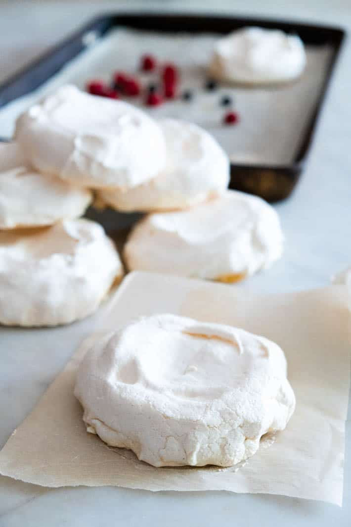 Baked meringues stacked in front of baking sheet.