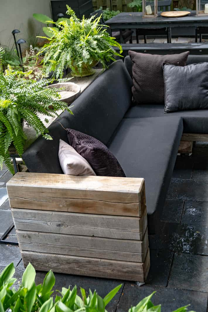DIY outdoor wooden Restoration Hardware sectional sofa with cushions in place beside potted ferns on table behind sofa.