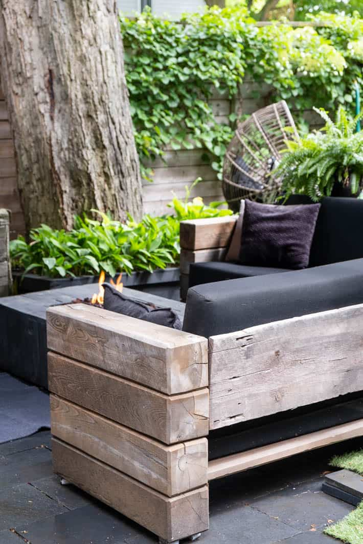 DIY outdoor wooden Restoration Hardware sectional sofa with cushions in front of lit backyard fire pit with large tree and wooden fence covered in greenery in background.