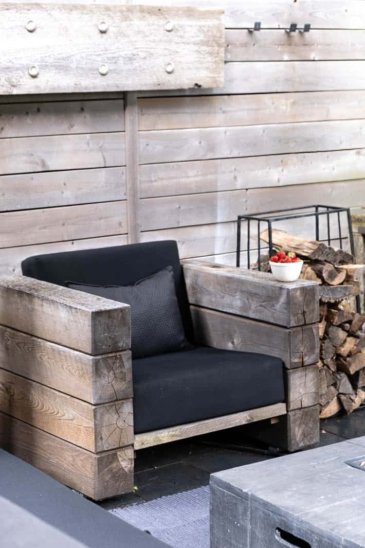 DIY outdoor wooden Restoration Hardware chair with stacked arms in front of horizontal running wood fence.