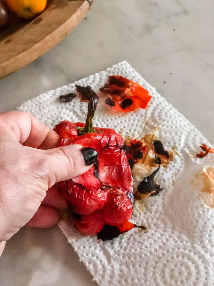 A woman's hand holds a charred roasted red pepper on a white paper towel sitting on a marble kitchen counter. Part of a wooden bowl containing tomatoes can be seen in the background.