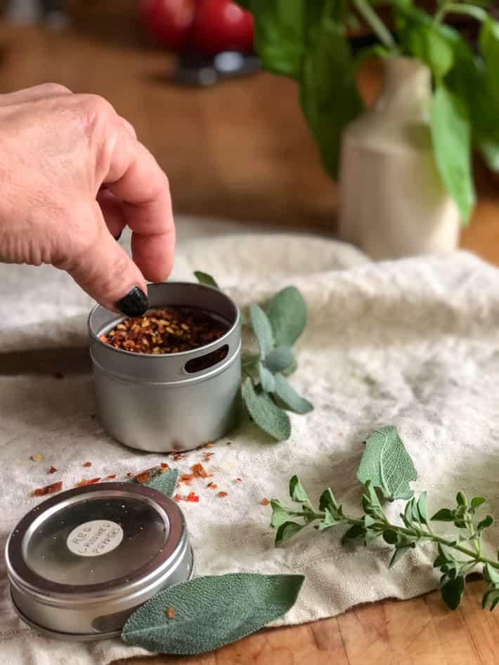 A woman's hand reaches for a tin container of dried red chili flakes sitting on a beige linen tea towel. Fresh sage and oregano seen in foreground. Background shows an ironstone jar containing fresh basil on a butcher block countertop.