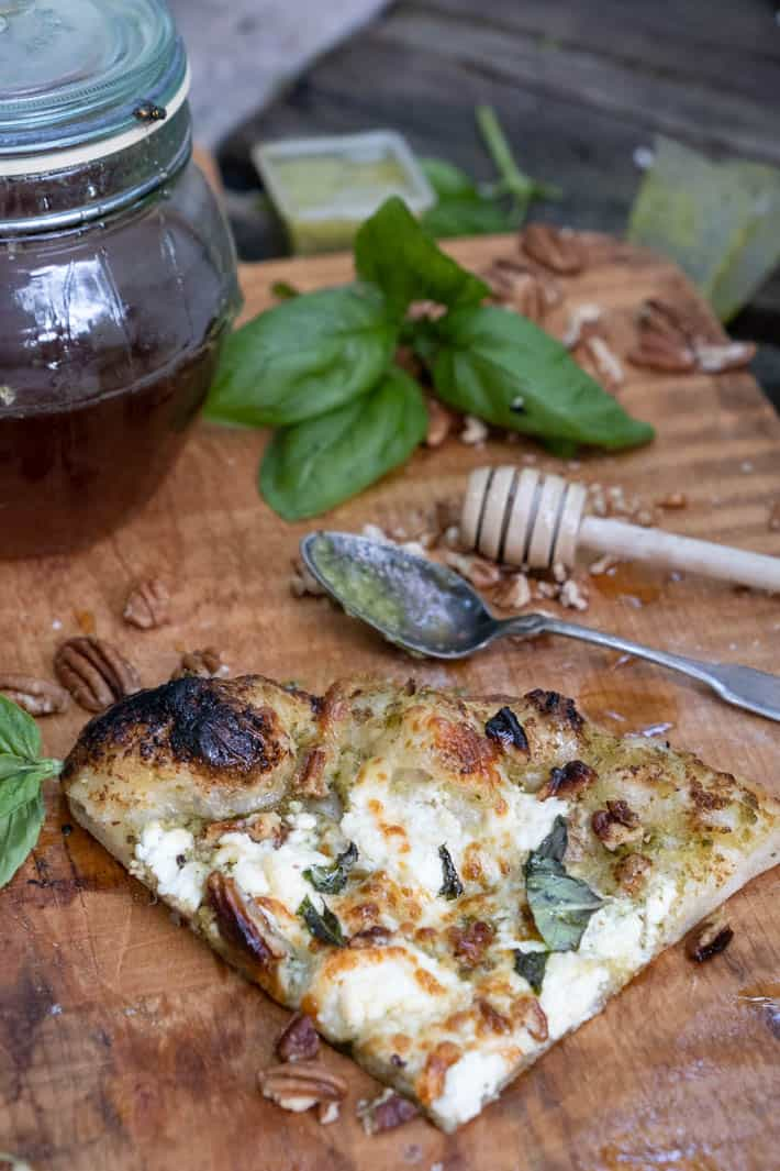 A slice of pesto pizza on wooden cutting board in foreground. Spoon covered with pesto, wooden honey dipper, fresh basil, pecans, containers of pesto and honey pot can be seen in background.