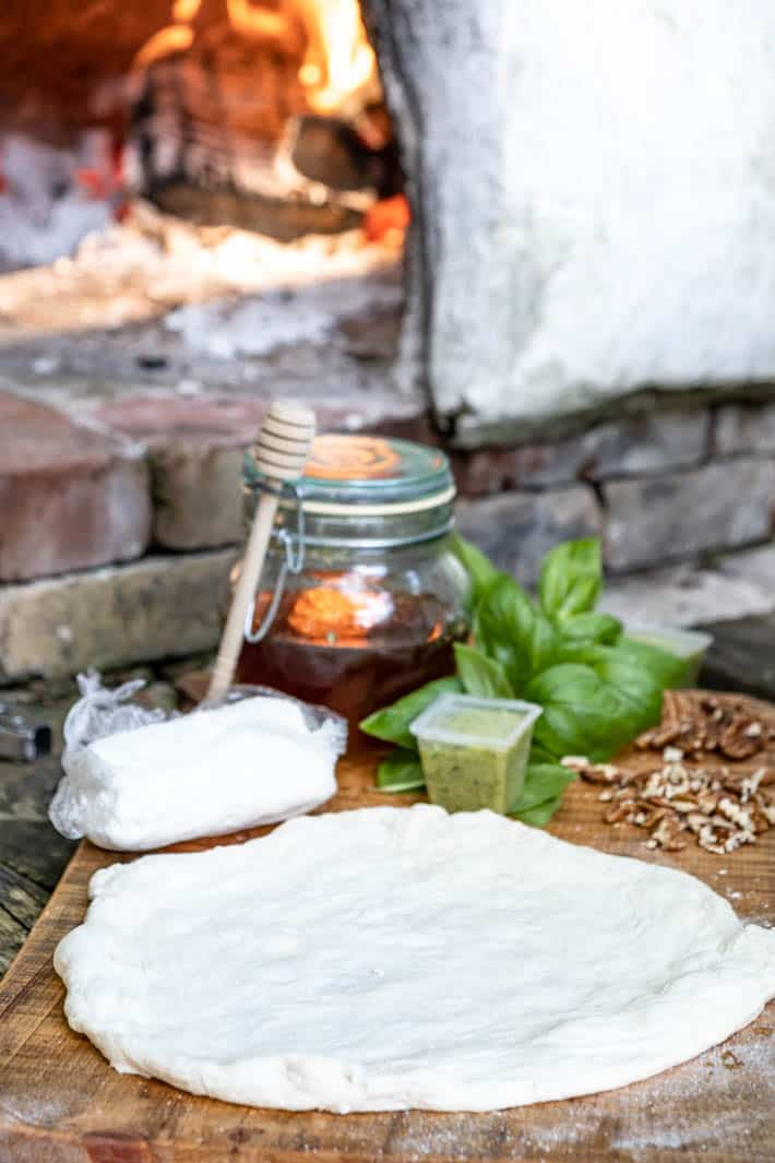 Disc of uncooked pizza dough, goat cheese, garlic scape pesto, pecans, fresh basil and a honey pot with honey dipper on wooden cutting board. Pizza oven with burning logs in it in background.