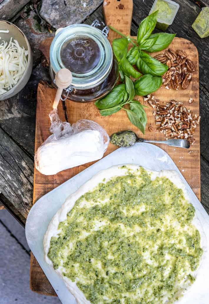 Overhead view of rolled out dough slathered with pesto on wooden cutting board. Also on board are goat cheese, chopped and whole pecans, bunches of fresh basil, and honey pot with honey dipper. Shredded mozzarella and containers of garlic scape pesto in background.