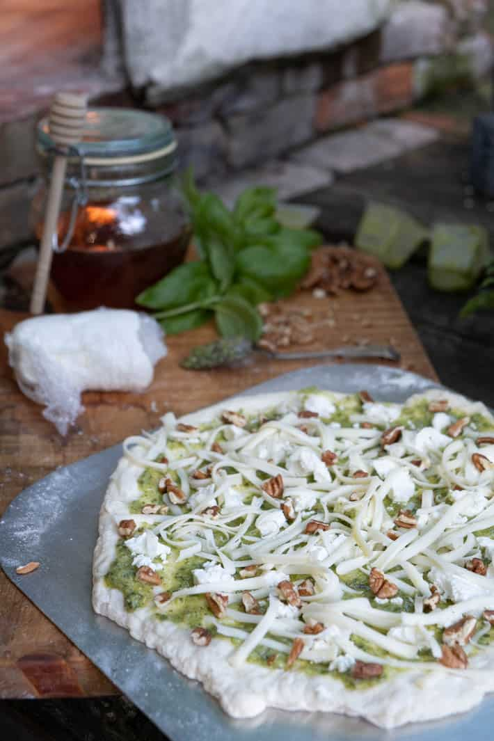 Uncooked pizza dough covered with pesto, chunks of goat cheese, mozzarella and chopped pecans on wooden cutting board in front of pizza oven.