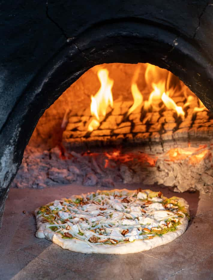Pizza being placed into wood-burning pizza oven.