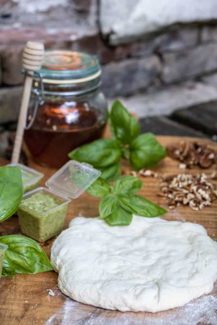 A disc of uncooked pizza dough on a wooden cutting board with a small container of garlic scape pesto, chopped and whole pecans, bunches of fresh basil and a honey pot with honey dipper.