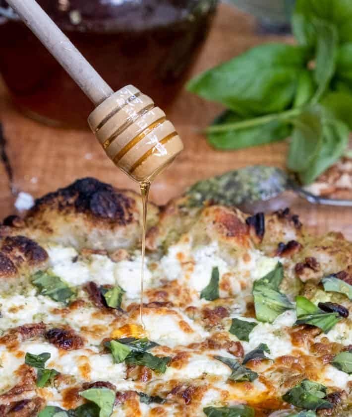 Close-up of the wooden honey dipper drizzling honey onto the freshly baked pesto pizza.