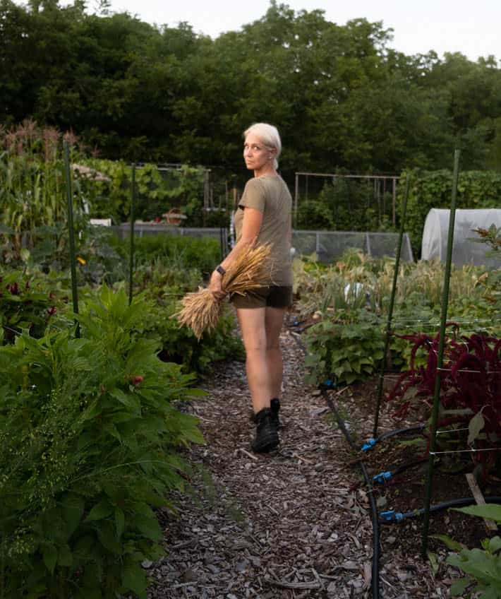 Karen Bertelsen walking away from the camera with her head turned toward the camera in her community vegetable plot.
